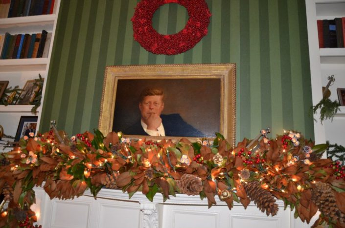 "Camelot Lives On: On loan from the National Gallery of Art in Washington, D.C., a portrait of former President John F. Kennedy by Jamie Wyeth hangs above the mantel. The room's bookshelves are filled with photos of the vice president's home from years past to celebrate the theme of ""Holidays Past and Present."" Number One Observatory Circle, the official home and residence of the Vice President of the United States. Photographer: Ken Cedeno/HGTV/Scrips Networks. Text credit: HGTV."