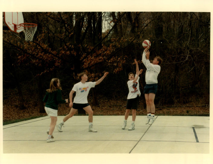 Shooting Hoops: Vice President Dan Quayle playing basketball with his three children (Corrine Quayle, Ben Quayle, and Tucker Quayle) on the grounds of the U.S. Naval Observatory. Number One Observatory Circle, the official home and residence of the Vice President of the United States. Photographer: Steven Purcell. Text credit: Charles Denyer.